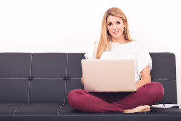 Smiling young woman looking on your laptop sitting on sofa at ho