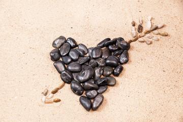 cœur de galets dessiné sur le sable