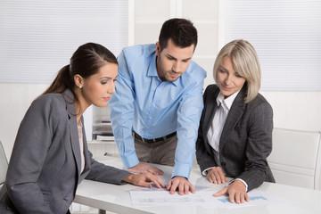 Kaufleute sitzen gemeinsam am Tisch und blicken auf Report