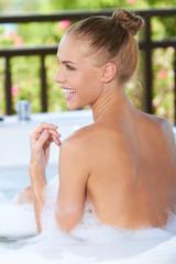 Happy woman enjoying a bubble bath