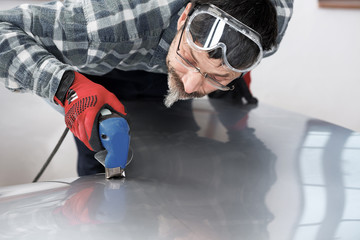 Cutting a stainless steel panel with an electric powered snips