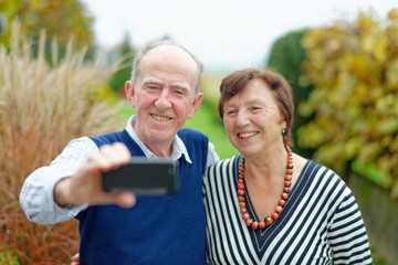 Happy senior couple bonding to each other and making selfie