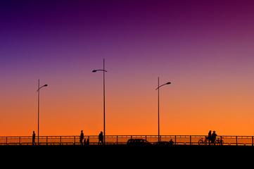 People on the bridge in sunset