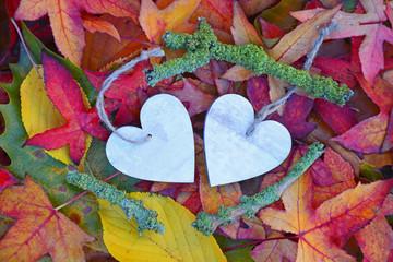 twee houten harten met herfstbladeren
