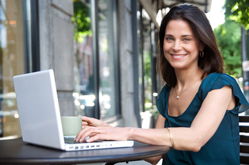 Smiling woman outdoors with laptop