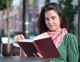 Woman looking up from her book at a sidewalk cafe