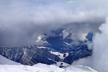 Top view on winter snowy mountains in clouds