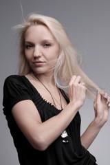 blonde girl posing in studio hair developing on a wind