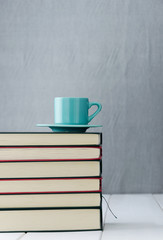 Blue coffee cup on stack of books