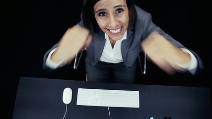 Woman works at the computer with joy