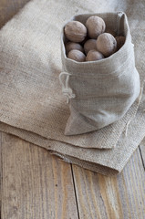 Walnuts in a canvas bag on a piece of burlap.