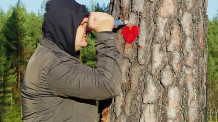 Angry man holding knife and fabric heart near the tree
