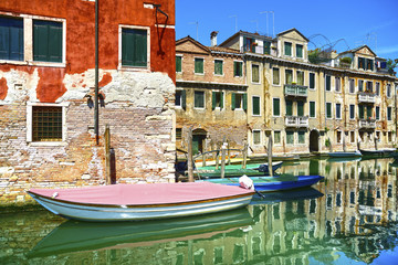 Venice cityscape, water canal, boats and traditional buildings.