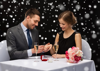 smiling couple with red gift box at restaurant