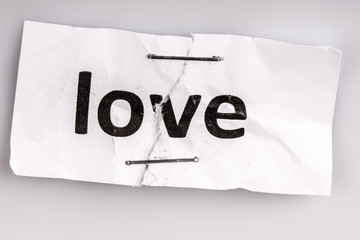 """""""Love"""" word written on torn and stapled paper"""