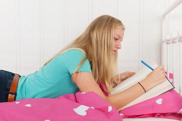 Making homework laying at bed