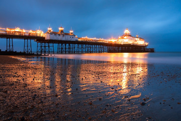 Eastbourne pier at dusk reflecting on a wet sand.