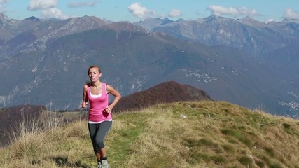 Woman running uphill on mountain trail