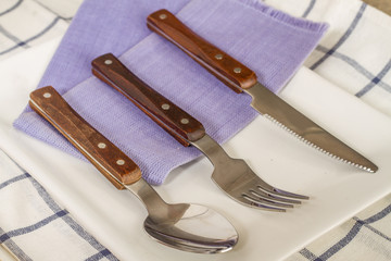 Forks and spoons and knives laid out on a plate.