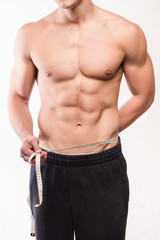 Muscular fitness man measuring his waist