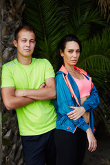 Fit man and sporty woman in fluorescent sportswear at workout
