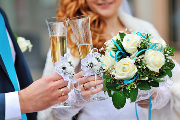 Two wedding glasses with champagne in hands of bride and groom