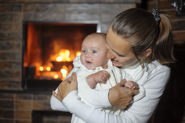 mother with her daughter at the fireplace