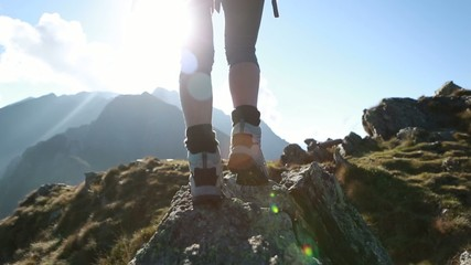 Hiker walks along narrow summit ridge crest, arms outstretch