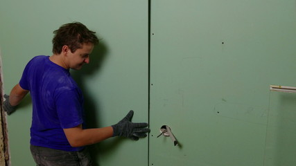 Repairer Make Install Drywall using Screwdriver and Screw, close
