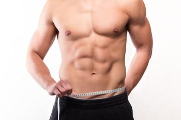 Muscular fitness man measuring his waist