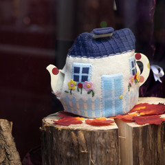 Teapot with knitted cosy with clipping path on wooden table