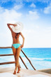 Back of beautiful woman in bikini with white hat