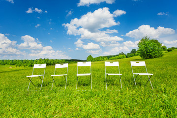 Five white chairs stand in a row on green grass