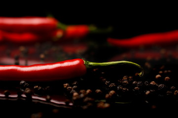 Studio shot of chilli peppers and black pepper on black