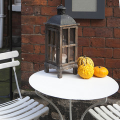 wooden lantern with pumpkins as a decoration of interiour