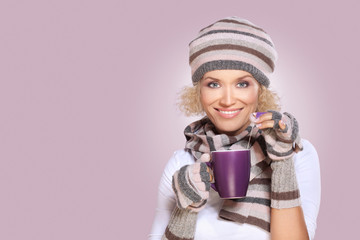 Woman in winter clothes drinking tea
