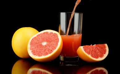 Studio shot sliced grapefruits with poured juice on black