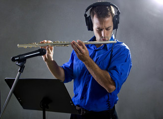 male flute player in a recording studio with headphones