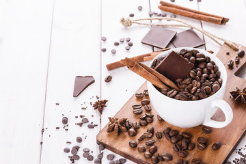 Coffee beans, spices and chocolate over white background