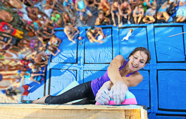 Female climber holding top handhold while winning contest