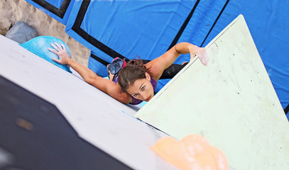Female climber on artificial climbing wall, view from above