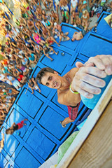 Rock climber holding top handhold while winning contest