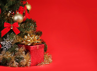 Christmas. Gift Box under Christmas Tree over Red Background.