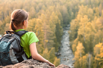 Young backpacker looking into the distance from mountain peak