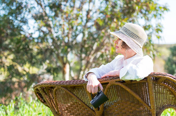 Woman sitting  on a bench in  the garden