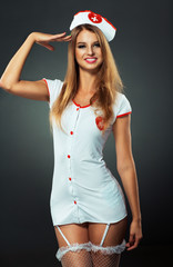 Young and beautiful dancer in nurse costume posing on studio