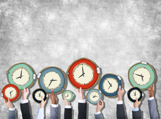 Group of Hands Holding Clock