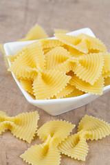 farfalle raw pasta on wooden table