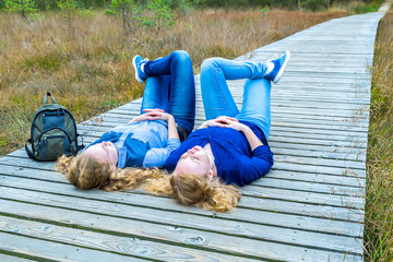 Two girls lying on their backs in nature