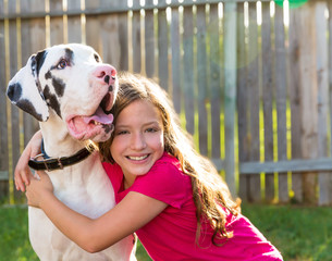 great dane and kid girl hug playing outdoor